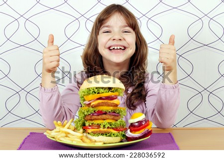 happy little girl with big hamburger and thumbs up - stock photo