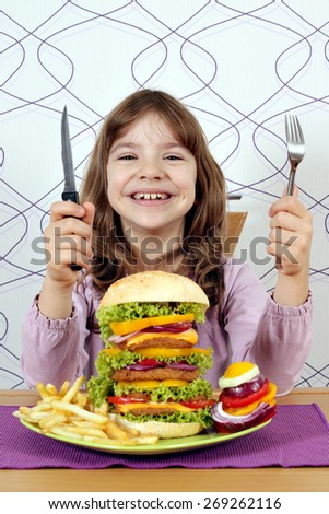 happy little girl with big hamburger ready for lunch - stock photo