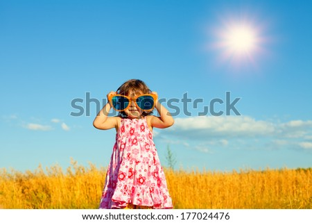 Happy little girl with big sunglasses in the wheat field - stock photo