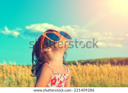 Happy little girl with big sunglasses looking at the sun - stock photo