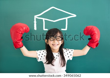 happy little girl with  boxing gloves and graduation concept - stock photo