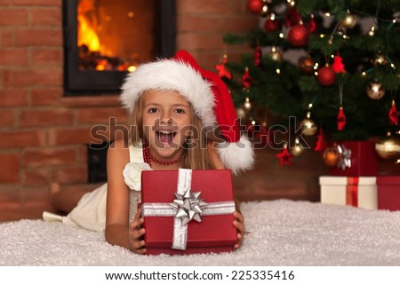 Happy little girl with Christmas present laying by the fire in front of xmas tree - stock photo