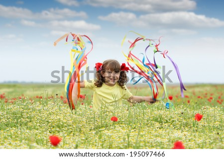 happy little girl with colorful ribbons on field