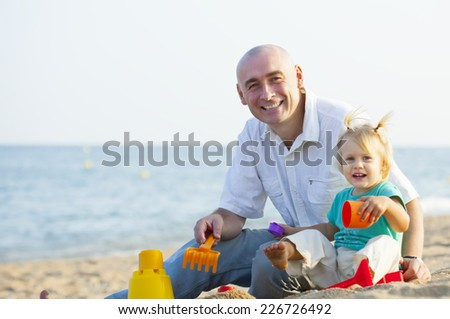 Happy little girl with dad playing on  sea shore - stock photo