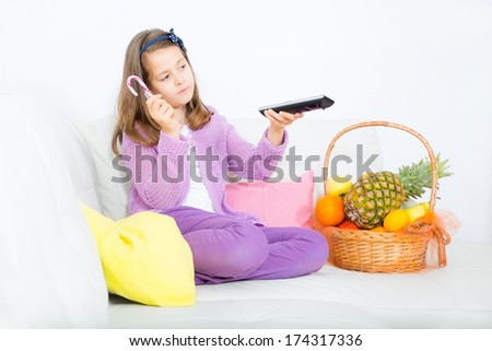happy little girl with fruits and lolipop - stock photo