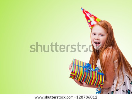 happy little girl with gift box on green   background - stock photo
