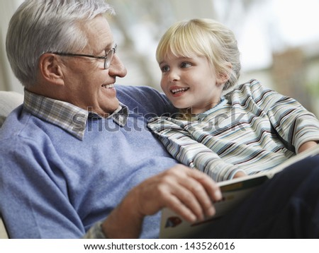 Happy little girl with grandfather reading story book at home - stock photo