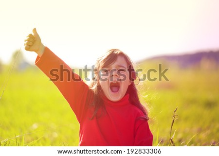 Happy little girl with hand up on the meadow in sunny day - stock photo