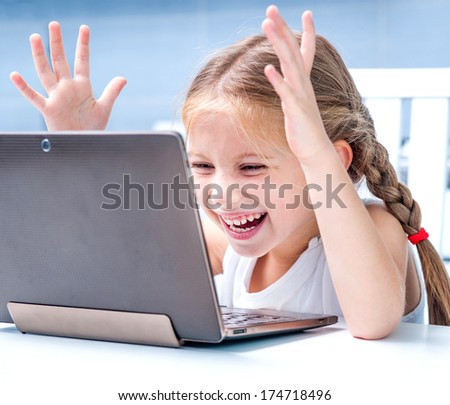 happy little girl with her computer at home at the table - stock photo