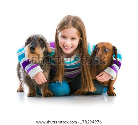 happy little girl with her ??dachshund in the studio on a white background