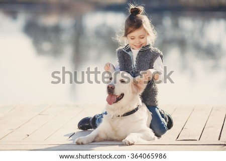 happy little girl with her dog golden retriever sitting on the bridge by the river. Cute little girl hugging golden retriever, smiling. The child with dogs. Puppies and child outdoor. - stock photo