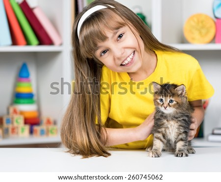 Happy little girl with her kitten at home at home - stock photo