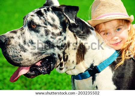 Happy little girl with her mastiff dog on a meadow in summer day. - stock photo