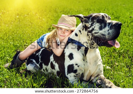 Happy little girl with her mastiff dog on a meadow in summer day. Countryside. - stock photo