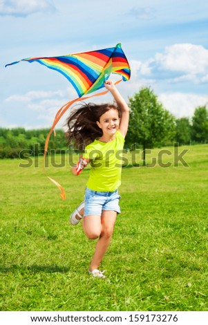 Happy little girl with kite running in the park with kite with smile and long hairs waiving on the wind