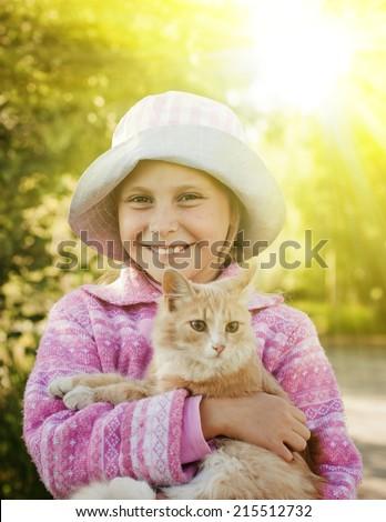 Happy little girl with kitten outside. - stock photo