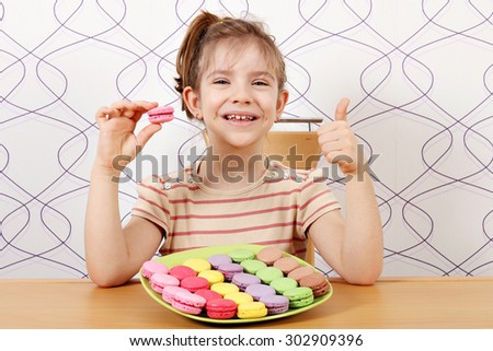 happy little girl with macaroons and thumb up - stock photo