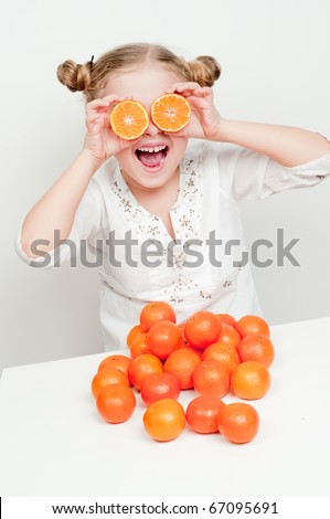 happy little girl  with orange mandarin - stock photo