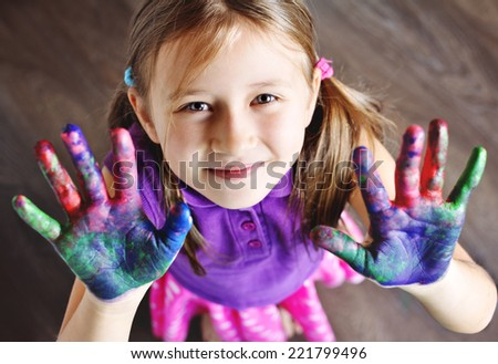 Happy little girl with painted hands. - stock photo