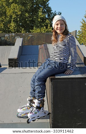 happy little girl with roller skates on playground - stock photo