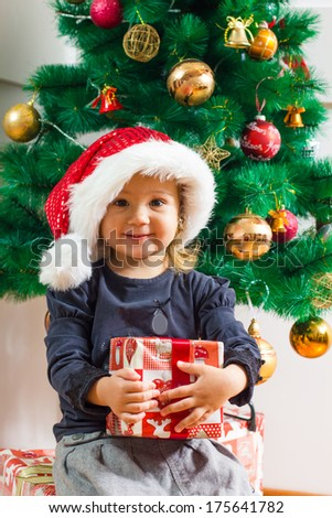 Happy little girl with Santa hat holding a Christmas gift at home.