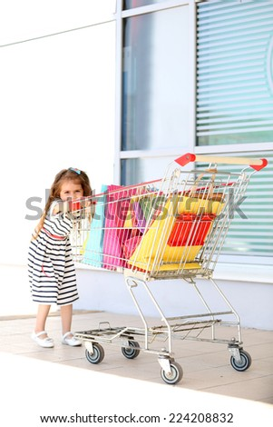 Happy little girl with shop bags in supermarket trolley, outdoors - stock photo