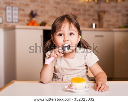 happy little girl with spoon and cake