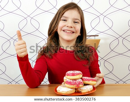 happy little girl with sweet donuts and thumb up - stock photo