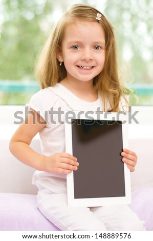 Happy little girl with tablet computer - stock photo