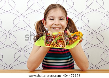 happy little girl with tacos for lunch - stock photo