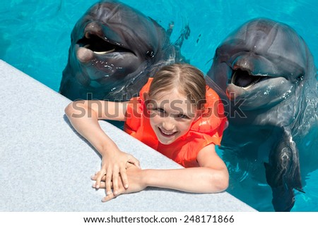 Happy Little Girl with two Dolphins in Swimming Pool