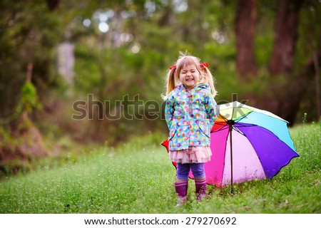 Happy little girl with umbrella in raincoat at green grass background at sunny day - stock photo