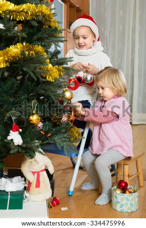 Happy little girls decorating Christmas decorations on New Year tree at home