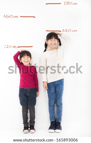 Happy little girls growing up and against the wall - stock photo