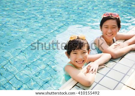happy little girls having fun  in swimming pool - stock photo