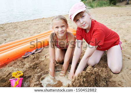 Happy little girls play on sand beach at summer