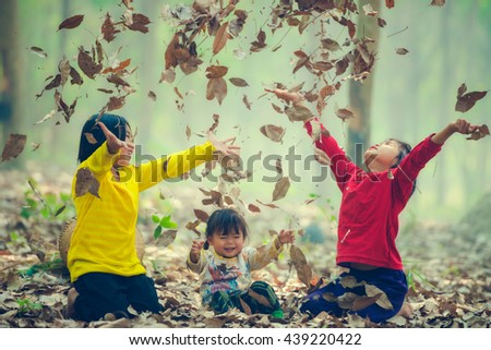 Happy Little girls playing on autumn leaves - stock photo