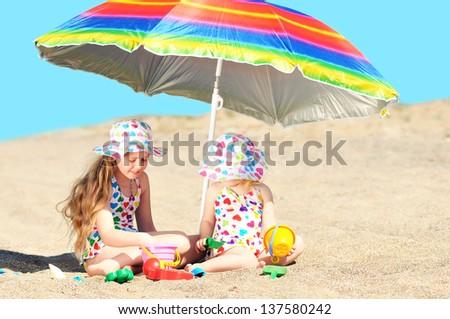 Happy little girls playing on beach - stock photo