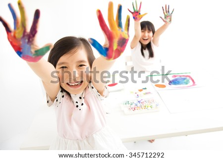 happy little girls with hands in the paint - stock photo