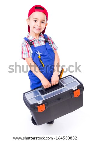 Happy little handyman boy carrying big toolbox and pliers in pocket - stock photo
