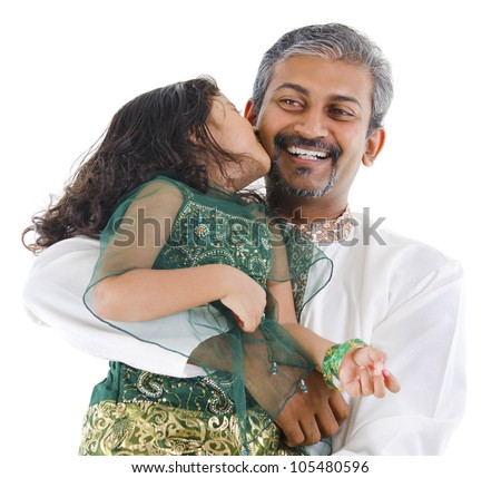 Happy little Indian daughter kissing her father on white background - stock photo