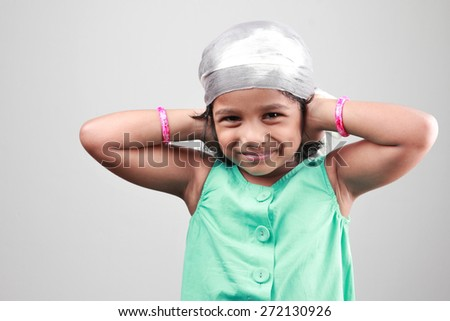 Happy little Indian girl poses with hands on her ears - stock photo