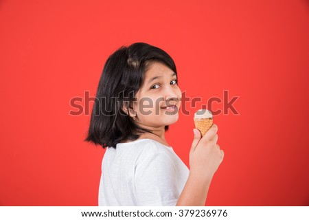 happy Little Indian girl with an ice candy or ice cream in hand, asian girl and ice cream, isolated on red background - stock photo