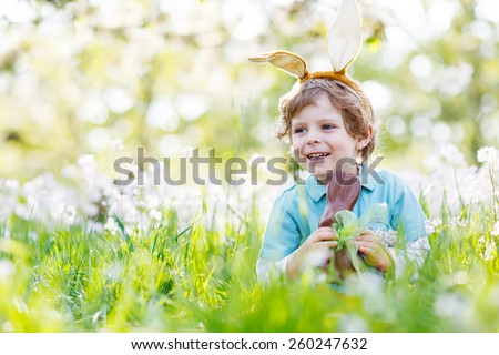 Happy little kid boy eating chocolate and wearing Easter bunny ears, sitting in blooming garden on warm sunny day. Celebrating Easter traditional holiday. - stock photo