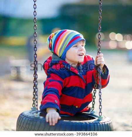 Happy little kid boy having fun with chain swing on outdoor playground. child swinging on warm sunny spring or autumn day. Active leisure with kids. Boy wearing colorful clothes - stock photo