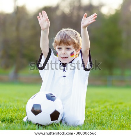 Happy little kid boy  having fun with playing soccer with football on field, outdoors. In white German national uniform and painted  flag on face. Beautiful child about european championship - stock photo