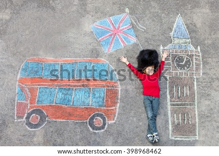 Happy little kid boy in british queen's guard soldier uniform having fun with London picture drawing with colorful chalks. With Big Ben, Union Jack and red bus. - stock photo