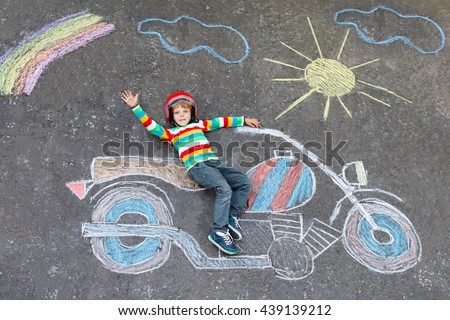 Happy little kid boy  in helmet having fun with motorcycle picture drawing with colorful chalks. Children, lifestyle, fun concept. child dreaming of future and profession.