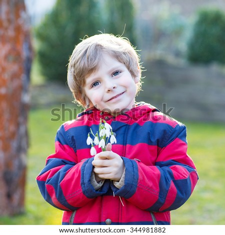 Happy little kid boy in red jacket holding snowdrop flowers outdoors on sunset. Child making gift for mum and dad.
