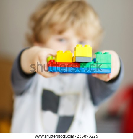 Happy little kid boy playing with construction blocks with created tower. Selective focus on toy - stock photo